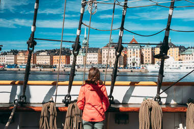 woman looking out from a ship on a european old town