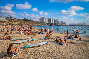 people lounging on a beach with a city in the background