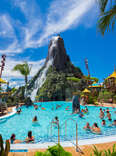 people in the wave pool in front of a giant volcano at a waterpark