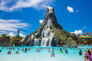 people swimming in front of a fake volcano at Volcano Bay Universal Studios