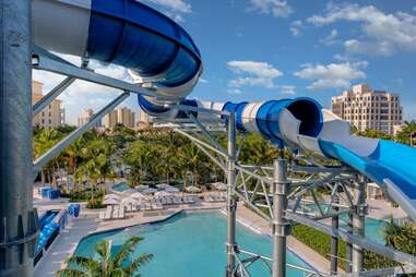 a water slide winding past a hotel, pool, and palm trees