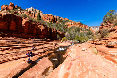 people gathered around and swimming in a river surrounded by red rock cliffs