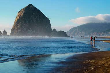 people walking along the beach near a giant rock