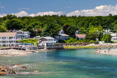 people playing on a beach in front of a Maine beach house