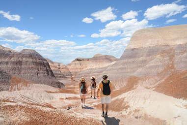 people walking through a deserted landscape