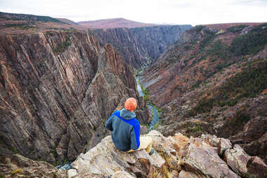 person sitting on a cliff overlooking a deep canyon river