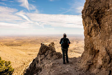 person standing on a cliff overlooking a vast desert