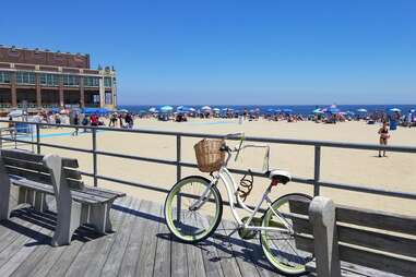 a bike parked in front of a busy beach