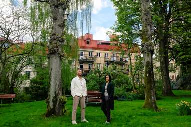 a man and a woman standing beneath a grove of trees near a large house