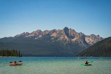 people canoeing on a mountain lake