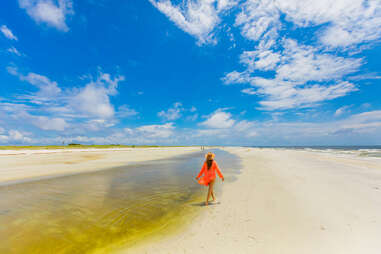 woman walking down the shores of a shallow beach