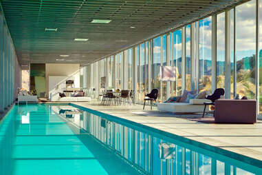 a giant indoor pool with couches overlooking a desert