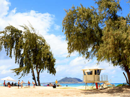 people having a beach day in Hawaii with a lifeguard cabana nearby