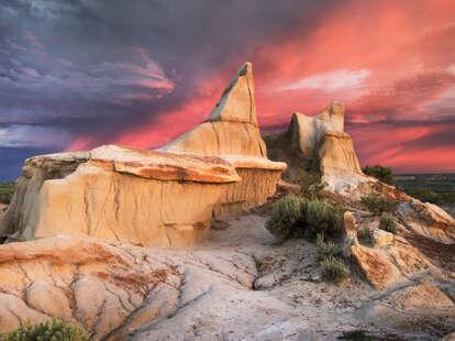 Clearing storm at sunrise over badlands sandstone formations