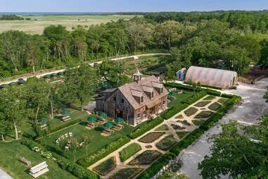 a farm in the middle of a garden on a stretch of land near the beach