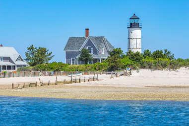 Sandy Neck Lighthouse dotting the blue coast of Cape Cod Bay along a sandy beach