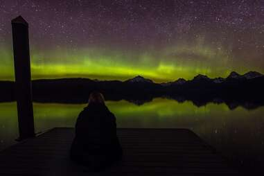 a person looking out at the northern lights above mountains