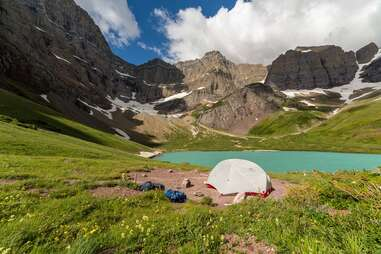 A tent set up in front of a blue-green lake and towering snowy mountains.
