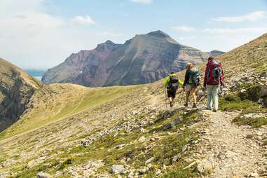 Three hikers on a trail facing large mountains in the distance