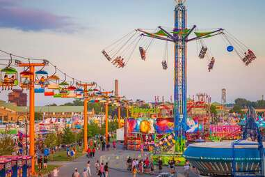 people riding carnival rides and walking the grounds of a state fair