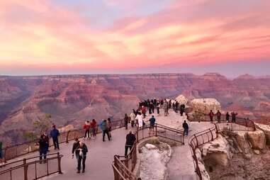 a crowd of people standing on the edge of the grand canyon