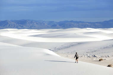 person walking across white sand dunes with mountains in the distance