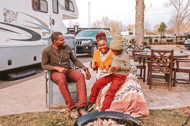 a family wearing cozy winter gear outside an rv sitting fireside