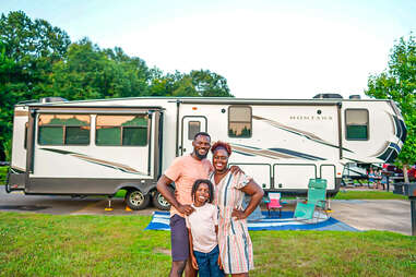 a family posing outside of their RV near a forest