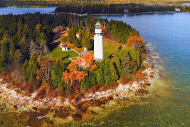 a lakeshore lighthouse surrounded by fall foliage