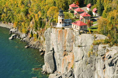 split rock lighthouse on a cliff above fall foliage