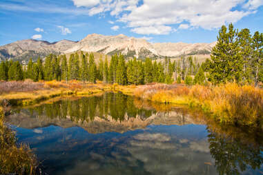 a mountain and fall foliage reflected in a river beneath a clear sky