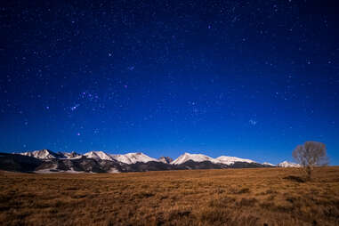 mountains and a field on a starry night