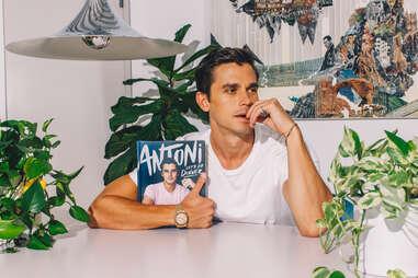Antoni holds his new cookbook