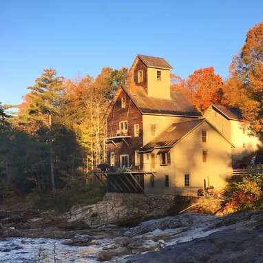 A historic grist mill perched atop Mill River waterfalls