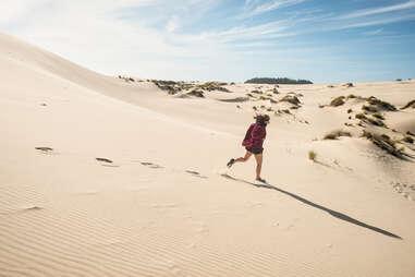 woman running down sand dunes