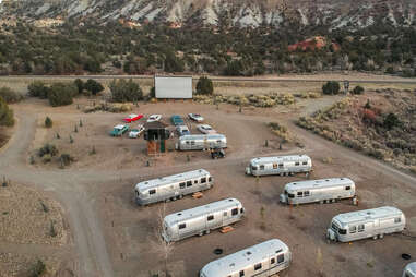 airstream trailers and a-frame cabins in the desert near a drive-in theater