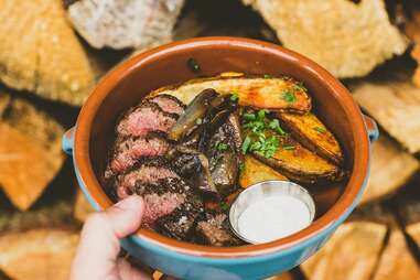 a bowl filled with steak and thick-cut fries