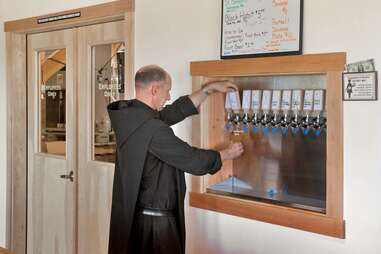 a monk pouring beer from a tap