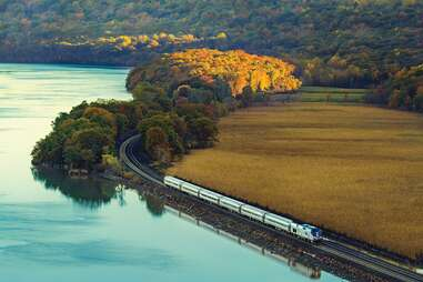 a train rolling along a lake in autumn