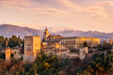 a large castle in front of snow-capped mountains