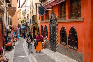 people walking down a narrow European street