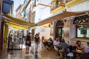 people walking past restaurants and diners on a narrow European street