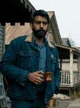 midnight mass, rahul kohli as sherrif hassan standing outside with coffee mug
