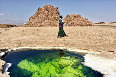Tour Guide next to the green water on the salt lake in the Danakil Depression in Ethiopa