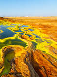 layered pools of colorful acid in the middle of a sweeping desert