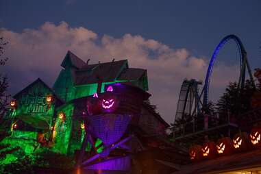 a Jack-O-Lantern with a rollercoaster in the distance