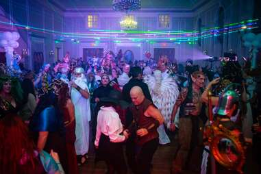 people dancing beneath an elaborate chandelier