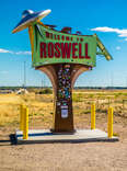 a sign for roswell, new mexico with a flying saucer on it in the desert