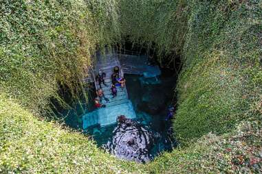 people swimming in an underground crystal spring