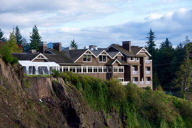 Captured with a tranquil overcast sky above, a hotel lodge sits proudly atop a cliff that overlooks the great Snoqualmie Falls